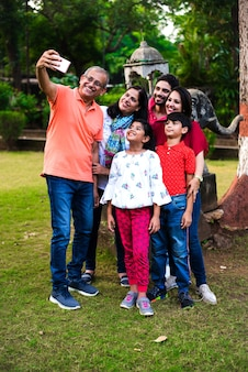 Indian grandfather taking selfie - multi generation asian family of six, capturing family photograph in smartphone while standing in garden or park