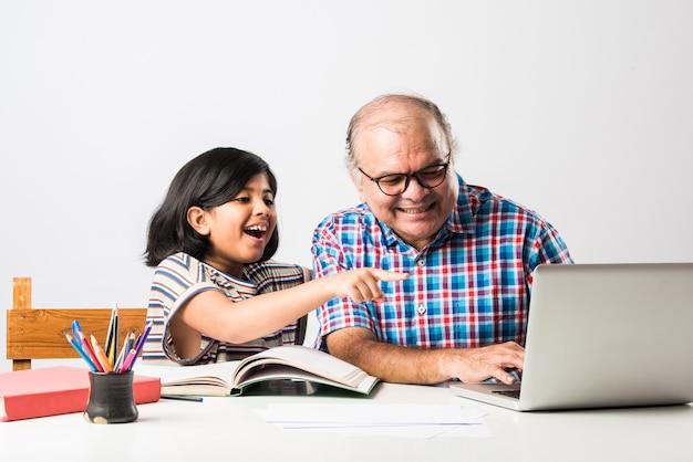 本、鉛筆とラップトップ、ホームスクーリングまたは授業料で孫娘を教えるインドの祖父