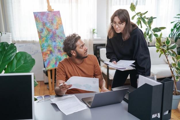 ノートパソコンと書類を持ったインド人の男がテーブルに座って、現代の事務室で白人女性の秘書と一緒に働いています。