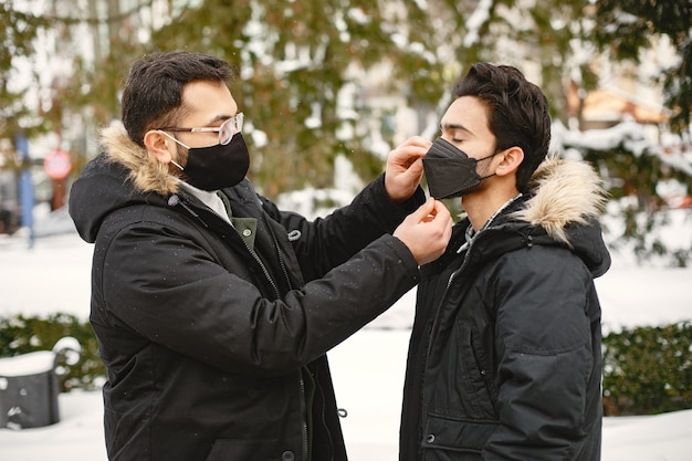 가면을 쓴 인도 사람들. 겨울에 거리에 남자. 소년들은 마스크를 쓴다.