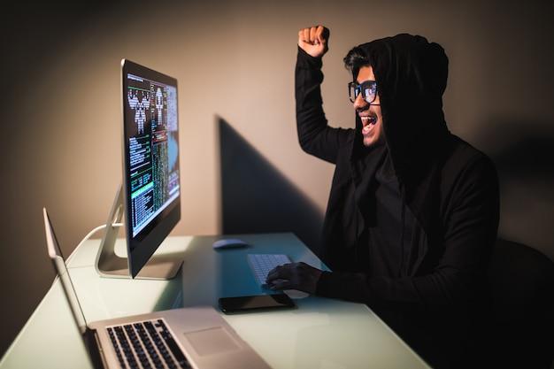 Il pirata informatico indiano indossa una maschera facendo uso di un computer portatile nella stanza bianca vuota.