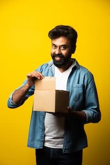 インドのハンサムなひげを生やした若い男が黄色の上に立っている間小包で箱を開く