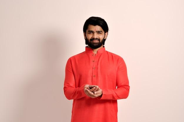 디왈리를 위해 디야를 들고 오렌지 쿠르타를 입은 인도의 잘생긴 남자