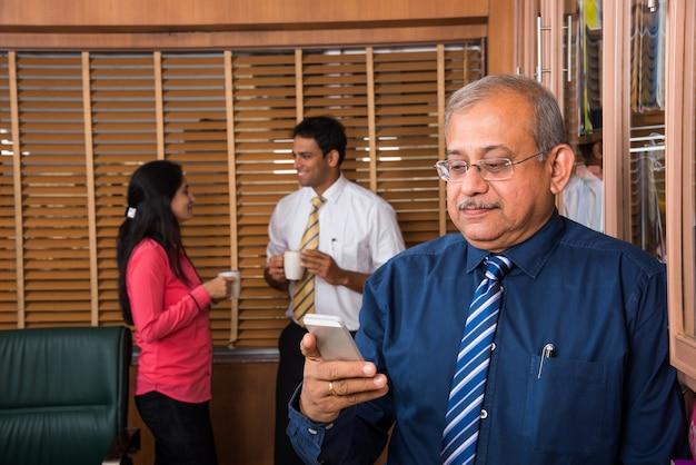 Индийский красивый старший бизнесмен, стоящий с руками в кармане, в то время как 2 молодых деловых человека пьют кофе и обсуждают на заднем плане