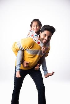 小さな娘とインドのハンサムな若い父親は白い背景に冬の服やセーターを着ています