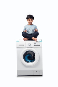 Индийский счастливый маленький мальчик позирует со стиральной машиной или посудомоечной машиной на белом фоне
