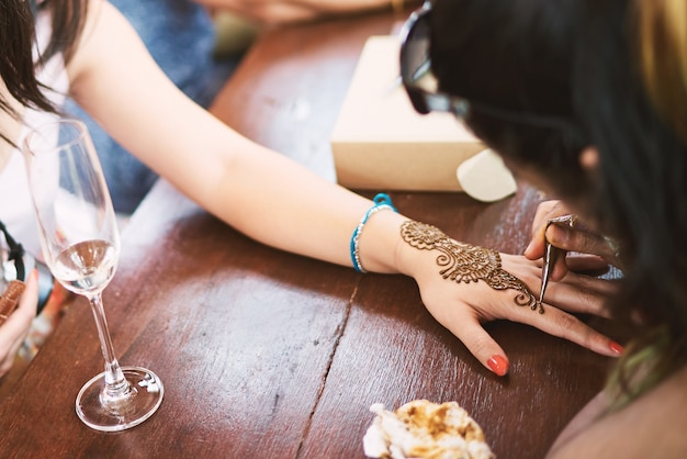 Indian henna tattoo artist drawing the uniqueness line art on the women hand