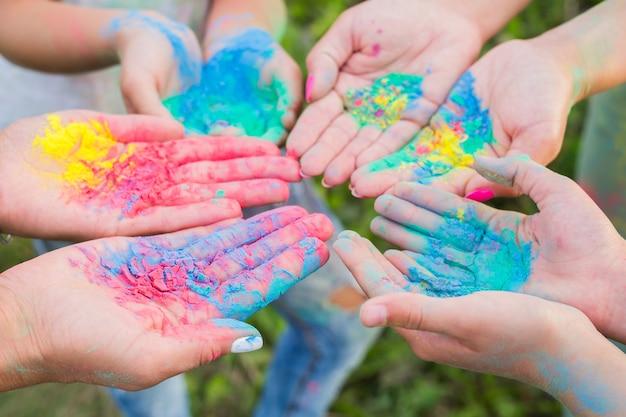 Индийские праздники, веселье и концепция фестиваля холи - женские ладони, покрытые разными цветами