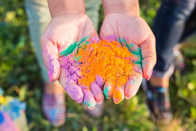 インドの休日、楽しさとホーリー祭のコンセプト-さまざまな色で覆われた女性の手のひら
