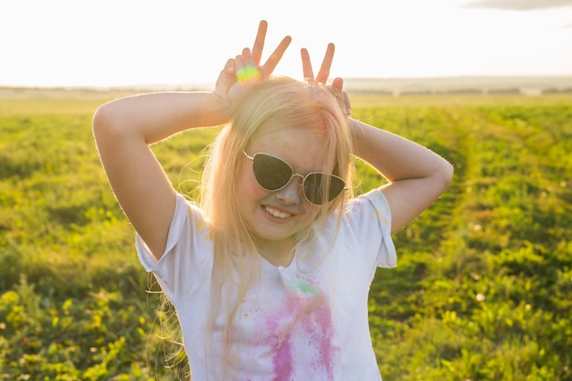 Indian holidays, fun and childhood concept - girl in glasses smiling, having fun on the holi festival.