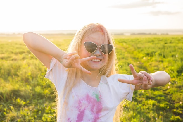 Indian holidays, fun and childhood concept - girl in glasses smiling, having fun on the holi