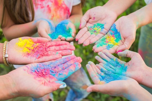 Индийские праздники, веселье, фестиваль холи и концепция людей - женские руки с разноцветной пудрой на фестивале холи