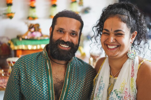 Indian husband and wife smiling - portrait of happy southern asian couple - love, ethnic and india's culture concept