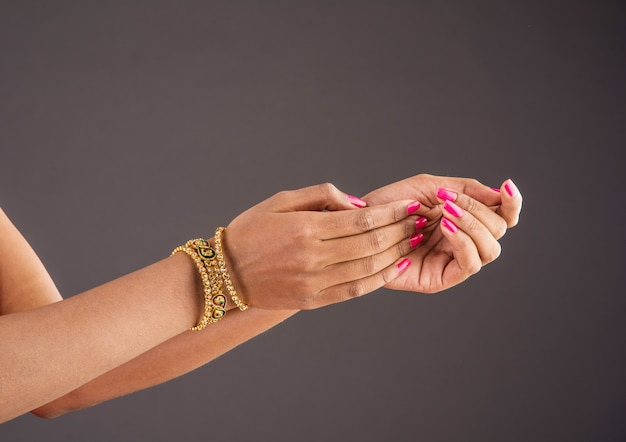 Indian jewellery - closeup of girl wearing traditional designer gold bangles or bracelets and showing graceful dance poses of hand over dark background, selective focus