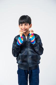 Индийский ребенок или мальчик ест мороженое в теплой одежде на белом фоне