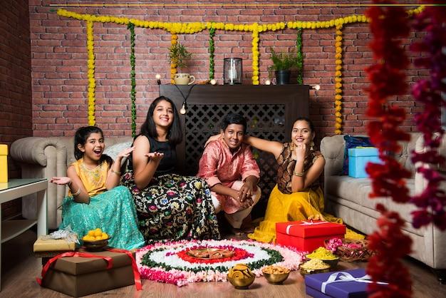 ディワリ、ディーパバリ、バイドゥージまたはラキまたはラクシャバンダンを花のランゴーリー、ギフト、ディヤで祝うインドの子供たち