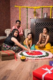 Indian kids celebrating diwali, deepawali, bhai dooj or rakhi or raksha bandhan with flower rangoli, gifts, diya
