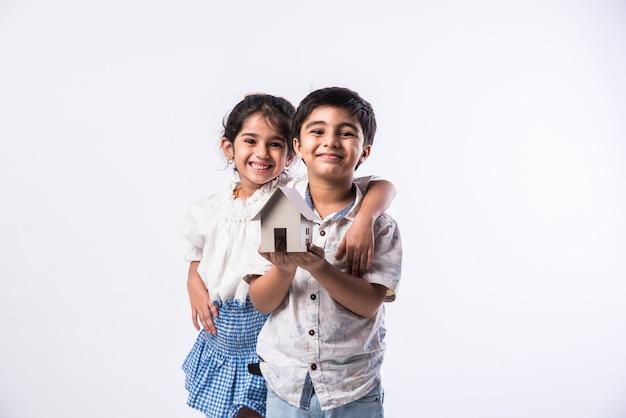 3d 종이 집 모델을 들고 인도 아이-공예 또는 부동산 개념을 보여주는