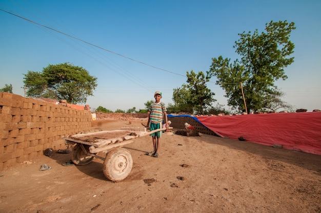 レンガ工場で伝統的なレンガで作るのを助ける労働者のインドの子供たち