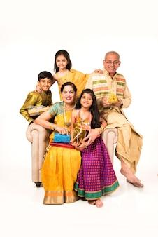 贈り物、お菓子とプージャまたはプージャターリーを持っているか、白い背景の上に隔離されたセルフィーを取る伝統的な服を着た祖父母を持つインドの子供たち
