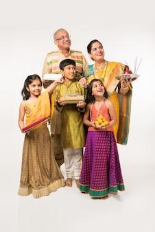 조부모와 함께 선물, 과자, 푸자 또는 푸자 탈리를 들고 흰색 배경에 격리된 셀카를 찍는 인도 아이들