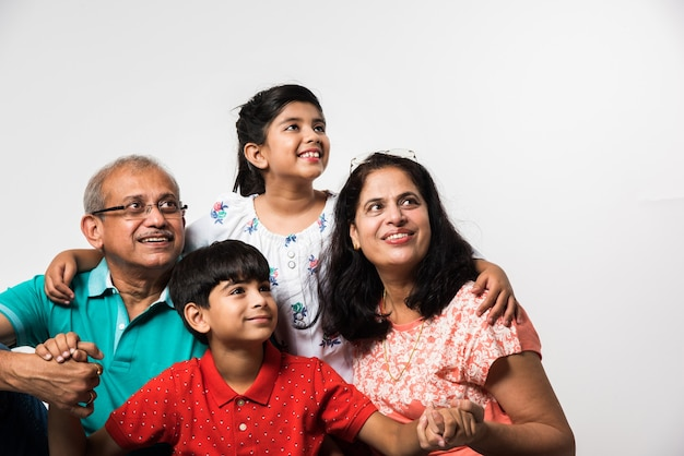 Индийские дети с бабушкой и дедушкой улыбаются, сидя на белом фоне в помещении, выборочный фокус