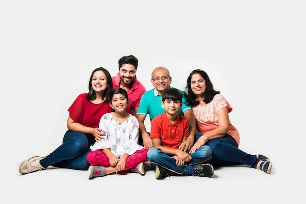 Индийские дети с родителями, бабушками и дедушками, сидя изолированно на белом фоне, студийный снимок