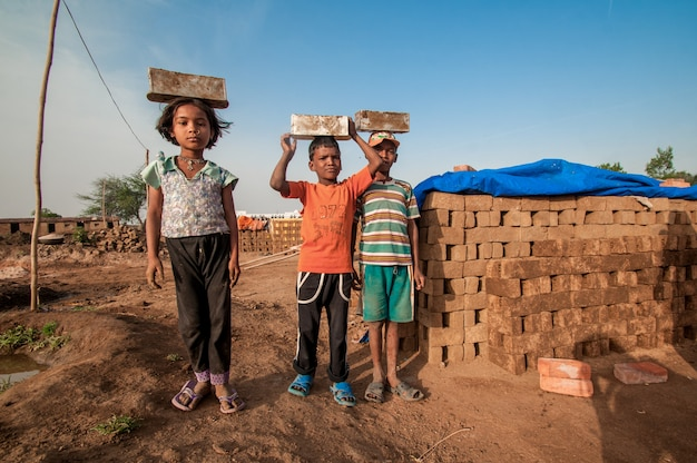 Indian kids of workers helping to make in traditional bricks by hand in the brick kiln or factory