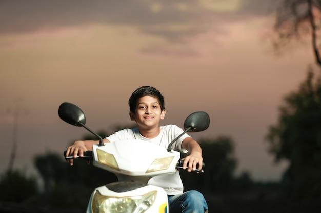 Indian little child riding motor bike