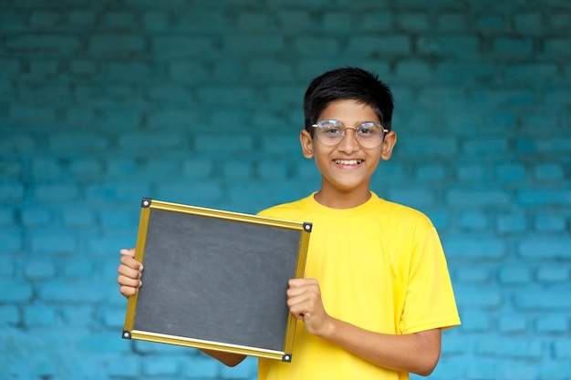Indian little child showing chalkboard with copy space