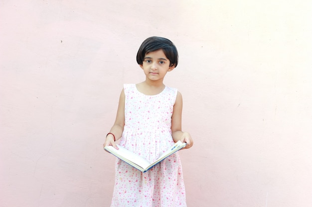 Indian little girl child writing on note book , studying