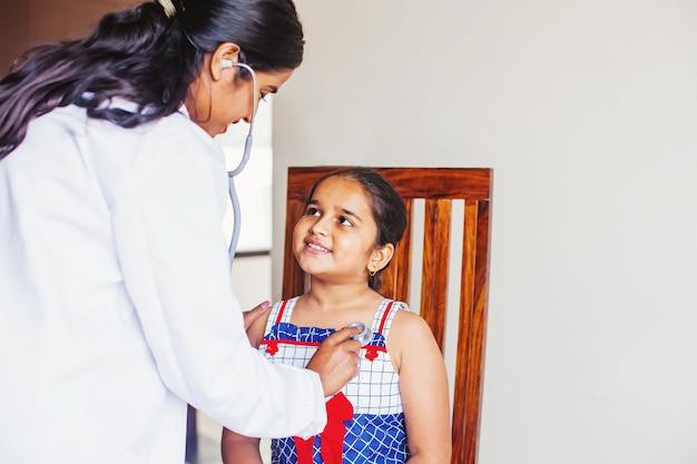 Индийская маленькая девочка в клинике на консультации врача
