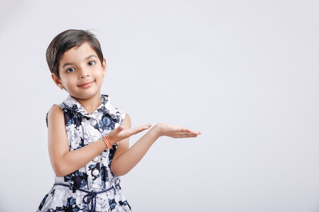 Indian little girl showing something with her hands. copyspace