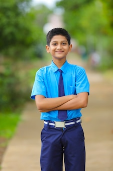 Indian little school boy giving expression over nature background.
