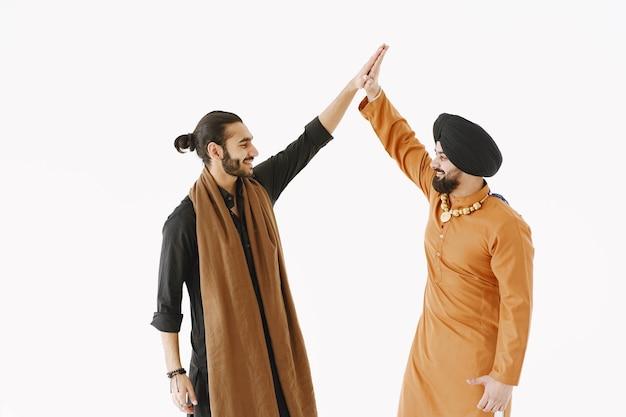 白い背景にインド人とパキスタン人。同意してハイタッチする。国家間の友情。