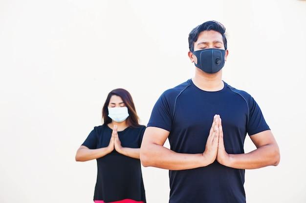 Индийский мужчина и женщина делают упражнения йоги в маске для лица