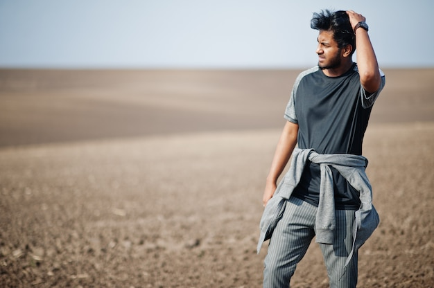 Indian man at casual wear posed at field alone.