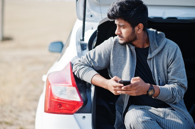 Indian man at casual wear posed at white car and looking at his mobile phone.