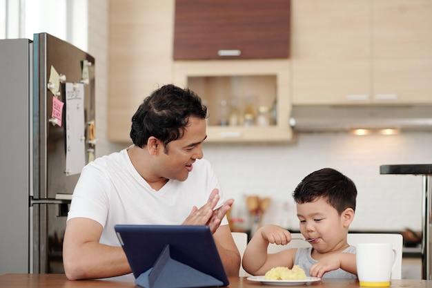 台所のテーブルで一人でマッシュポテトのプレートを食べる息子に拍手するインド人男性