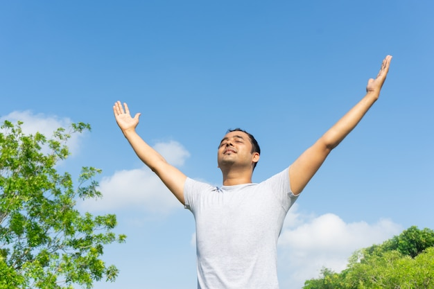 Индийский человек, концентрируясь и поднимая руки на открытом воздухе с голубым небом и зелеными ветвями деревьев