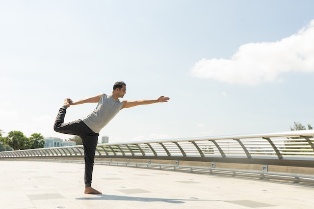 Indian man doing lord of dance pose outdoors on bridge on sunny day. city yoga concept.