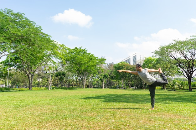 Indian man doing lord of dance pose outdoors in summer city park with trees