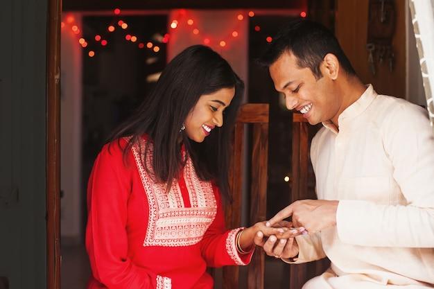 Indian man doing palm reading for a woman wearing kurta