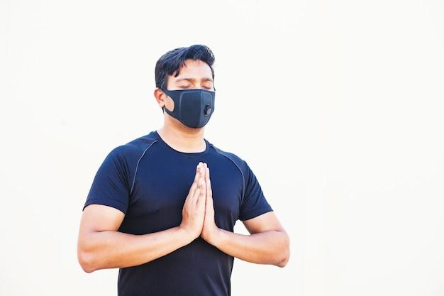Индийский мужчина занимается йогой и медитацией в маске для лица