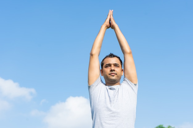 Indian man doing yoga and pressing hands together above head outdoors