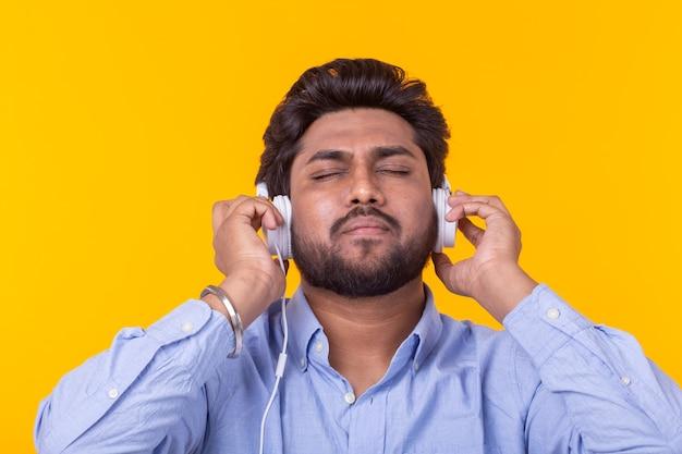 Индийский мужчина наслаждается музыкой в наушниках на желтой стене.