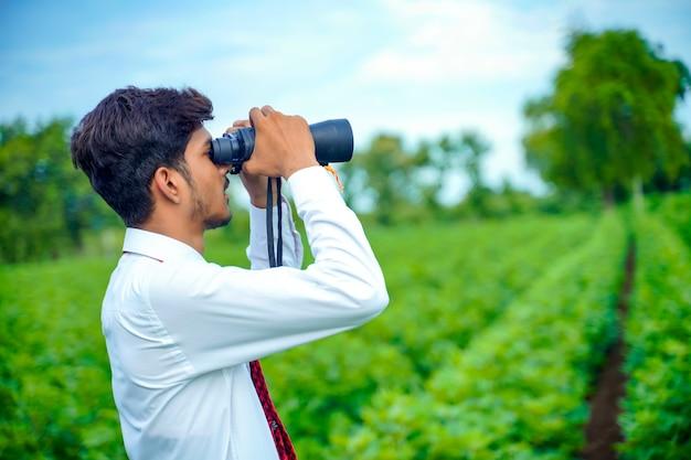 インドの男性は双眼鏡で自然の中で楽しんでいます