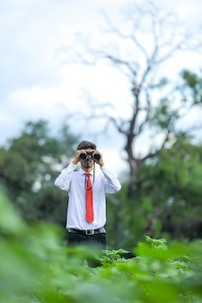 Indian man enjoys in nature with binoculars