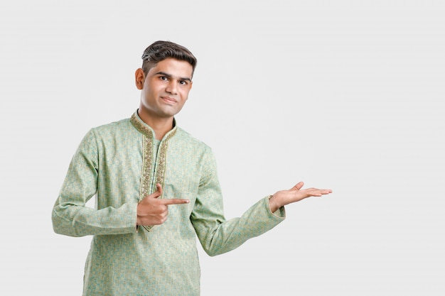 Indian man in ethnic wear and showing direction with hand