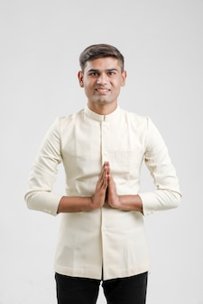 Indian man in ethnic wear and  showing a welcome gestures isolated on white